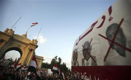 Protesters opposing Egyptian President Mohamed Mursi shout slogans near a banner with pictures of members of the Muslim Brotherhood during a protest in front of the Presidential Palace ''Qasr Al Quba'' in Cairo July 2, 2013. REUTERS/Amr Abdallah Dalsh
