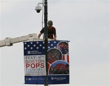 A worker installs a piece of security equipment on a lamp post on a bridge over the Charles River in Boston, Massachusetts July 2, 2013, in preparations for the city's Fourth of July celebrations. REUTERS/Brian Snyder