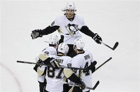 Pittsburgh Penguins Kris Letang (top) skates in to celebrate with teammates Pascal Dupuis, Sidney Crosby and Brooks Orpik (bottom L-R) after Crosby scored a goal against the Boston Bruins during the first period of their NHL hockey game at TD Garden in Boston, Massachusetts, April 3, 2012. REUTERS/Jessica Rinaldi