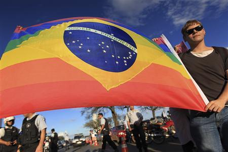 A gay activist carries a Brazil flag in rainbow colours in protest at the ''March For Family'' demonstration against abortion and gay marriage, in front of the National Congress in Brasilia June 5, 2013. REUTERS/Ueslei Marcelino (BRAZIL - Tags: POLITICS RELIGION CIVIL UNREST) - RTX10D80