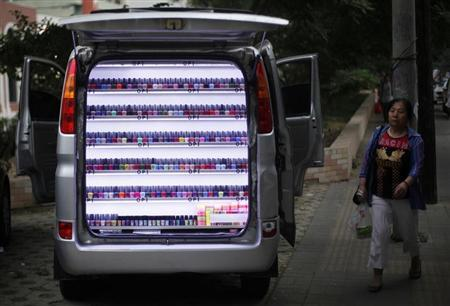 A woman walks past a van which has been converted into a stall selling nail polish on a sidewalk in Beijing, June 4, 2013. REUTERS/Barry Huang