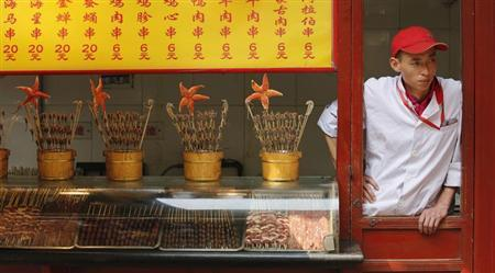 A food vendor waits for customers at a shopping district in Beijing May 6, 2013. REUTERS/Kim Kyung-Hoon