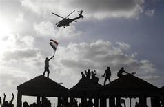 """Военный вертолет пролетает над сторонником президента Египта Мохамеда Мурси в Александрии 2 июля 2013 года. Главнокомандующий вооруженными силами Египта заявил о готовности к крайним мерам ради того, чтобы добиться ухода в отставку президента от правящей партии """"Братья-мусульмане"""" Мохамеда Мурси. REUTERS/Asmaa Waguih"""