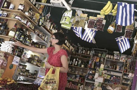 A woman buys products in a grocery market in central Athens July 2, 2013. REUTERS/John Kolesidis