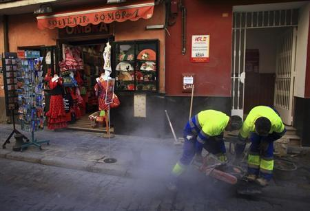 People work next to a souvenir shop in the Andalusian capital of Seville January 23, 2013. REUTERS/Marcelo del Pozo