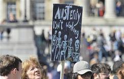 A protester holds a placard during a rally in Trafalgar Square in central London May 1, 2013. REUTERS/Toby Melville