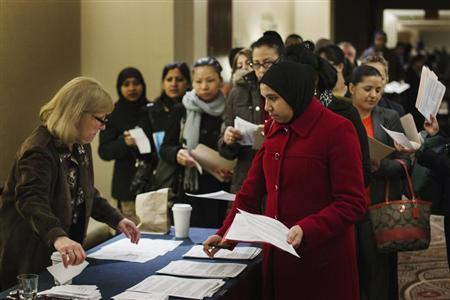 Job seekers adjust their paperwork as they wait in line to attend a job fair in New York February 28, 2013. REUTERS/Lucas Jackson