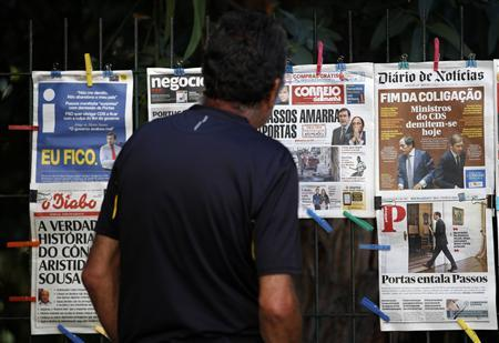 A man reads the front pages of various newspapers in Lisbon July 3, 2013. REUTERS/Hugo Correia