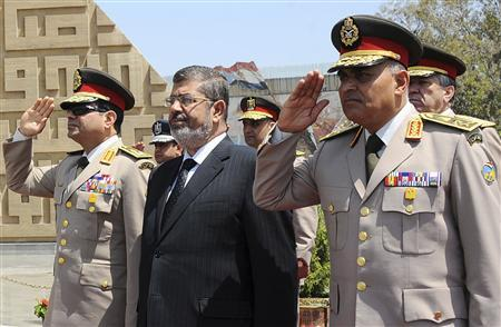 Egypt's President Mohamed Mursi (C) stands after laying a wreath during his visit to the tomb of former President Anwar al-Sadat and the Tomb of the Unknown Soldier during the commemoration of Sinai Liberation Day in Cairo, in this April 24, 2013 file photograph. REUTERS/Egyptian Presidency/Handout/Files