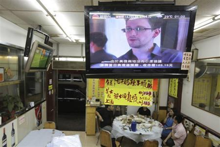 Edward Snowden, a former contractor at the National Security Agency (NSA), is seen during a news broadcast on television at a restaurant in Hong Kong June 26, 2013. REUTERS/Tyrone Siu