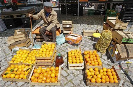 An orange farmer waits for customers at the Malveira village market, on the outskirts of Lisbon May 30, 2013. REUTERS/Jose Manuel Ribeiro