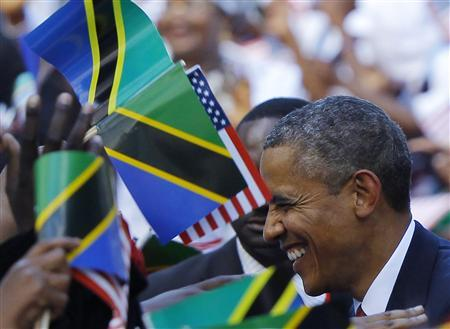 U.S. President Barack Obama is surrounded by Tanzanian and United States flags while greeting people at an official arrival ceremony in Dar Es Salaam July 1, 2013. REUTERS/Gary Cameron