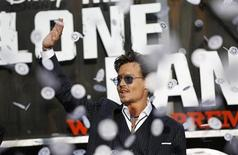 "Cast member Johnny Depp waves as confetti fly at the world premiere of ""The Lone Ranger"" at Disney California Adventure Park in Anaheim, California June 22, 2013. REUTERS/Mario Anzuoni"