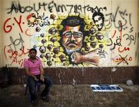 A protester, opposing Egypt's President Mohamed Mursi, sits next to graffiti depicting Mursi on a wall of the Presidential Palace in Cairo July 2, 2013. REUTERS/Khaled Abdullah