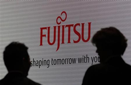 People are silhouetted against a screen displaying a logo of Fujitsu at CEATEC JAPAN 2012 electronics show in Chiba, east of Tokyo, October 2, 2012. REUTERS/Yuriko Nakao/Files