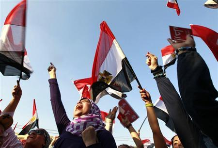 Protesters against Egyptian President Mohamed Mursi wave Egyptian national flags in front of the presidential palace in Cairo July 3, 2013. REUTERS/Louafi Larbi