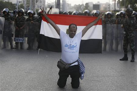 A member of the ''Tamarod - Rebel!'' petition drive against Mursi, gestures with an Egyptian flag in front of army soldiers standing guard in front of protesters who are against Egyptian President Mohamed Mursi, near the Republican Guard headquarters in Cairo July 3, 2013. REUTERS/Amr Abdallah Dalsh
