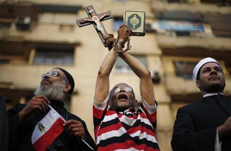 A protester holds a cross and Koran during a protest demanding that President Mohamed Mursi resign at Tahrir Square in Cairo July 1, 2013. REUTERS/Suhaib Salem