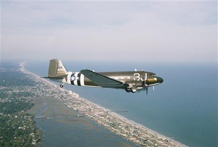 South Carolina pilot Barry Avent flies his World War II DC-3 C-47 cargo plane near Myrtle Beach, South Carolina in this 2008 file photo. Avent's C-47, which flew the English Channel during World War Two, will join other vintage warplanes on Thursday, July 4, 2013, in ''Salute from the Shore,'' a patriotic flight over the South Carolina coast, replacing the usual military jets which have been grounded for public events due to federal budget cuts. REUTERS/Ron Gantt/Handout via Reuters