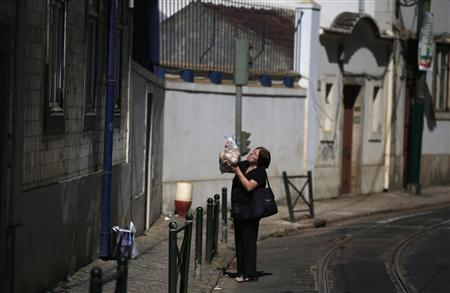 A woman offers a bag filled with bread to other woman (not pictured) at the Alfama neighbourhood in Lisbon July 3, 2013. REUTERS/Rafael Marchante