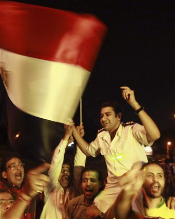 A policeman (C) cheers with protesters, who are against Egyptian President Mohamed Mursi, as they dance and react in front of the Republican Guard headquarters in Cairo July 3, 2013. REUTERS/Louafi Larbi