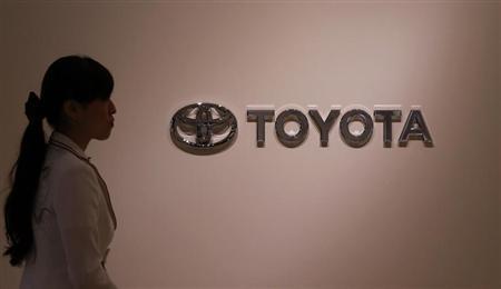 A woman walks past Toyota Motor's logo at the company showroom in Nagoya, central Japan July 1, 2013. REUTERS/Toru Hanai