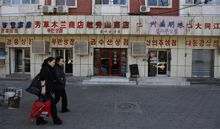 Women walk past shops with signboards written in Korean characters near the North Korean embassy in Beijing March 18, 2013 file photo. REUTERS/Kim Kyung-Hoon