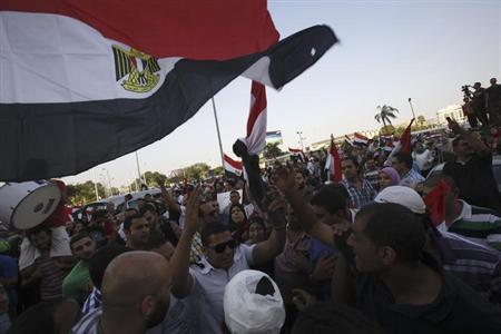 A policeman (L) cheers with protesters, who are against Egyptian President Mohamed Mursi, as they dance and react in front of the Republican Guard headquarters in Cairo July 3, 2013. REUTERS/Amr Abdallah Dalsh