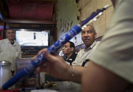 Egyptians sit in a Hookah Bar while watching and discussing the news in Egypt in the Queens borough of New York, July 3, 2013. REUTERS/Carlo Allegri