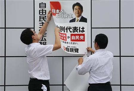 Staff members of Japan's ruling Liberal Democratic Party (LDP) post an election poster with the image of Japan's Prime Minister Shinzo Abe, who is also leader of the LDP, at the LDP headquarters in Tokyo July 4, 2013. REUTERS/Yuya Shino