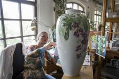 A woman paints on a vase at the KPM porcelain manufacturer in Berlin June 28, 2013. REUTERS/Thomas Peter