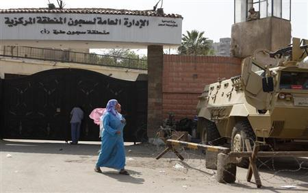 People and army soldiers stand outside a gate of the Torah prison, southern Cairo, April 13, 2011. REUTERS/Asmaa Waguih