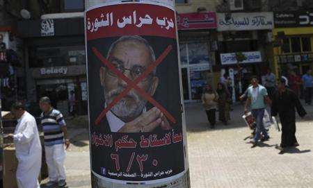 People walk past a defaced poster of Muslim Brotherhood leader Mohammed Badie with Arabic text which reads ''Together to down brotherhood's power'' near Tahrir Square in Cairo June 23, 2013. REUTERS/Amr Abdallah Dalsh