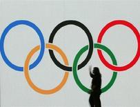 Operário trabalha na decoração do palco com os anéis olímpicos no centro de convenções de Cingapura. A capital da Argentina, Buenos Aires, vai sediar as Olímpiadas da Juventude de 2018, revelou o Comitê Olímpico Internacional (COI) nesta quinta-feira. 5/07/2005. REUTERS/Bazuki Muhammad