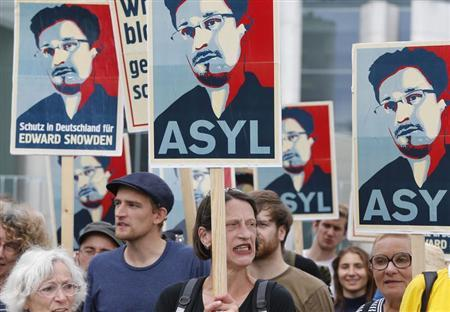 Demonstrators hold banner during protest rally in support of former U.S. spy agency NSA contractor Edward Snowden in Berlin July 4, 2013. REUTERS/Tobias Schwarz