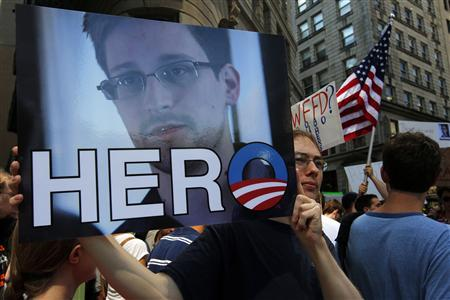 A demonstrator holds a sign with a photograph of former U.S. spy agency NSA contractor Edward Snowden and the word ''HERO'' during Fourth of July Independence Day celebrations in Boston, Massachusetts July 4, 2013. REUTERS/Brian Snyder