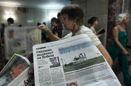 An employee distributes newspapers, with a photograph (L) of former U.S. spy agency contractor Edward Snowden seen on a page, at an underground walkway in central Moscow July 2, 2013. REUTERS/Maxim Shemetov