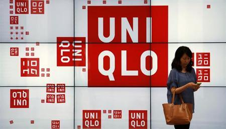 A woman checks her phone in front of a panel outside the flagship store of Japanese fashion house Uniqlo at Hong Kong's Causeway Bay shopping district May 9, 2013. REUTERS/Bobby Yip