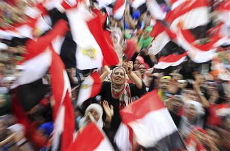 Protesters against ousted President Mohamed Mursi wave Egyptian flags in Tahrir Square in Cairo July 4, 2013. The leader of the Muslim Brotherhood was arrested by Egyptian security forces on Thursday in a crackdown against the Islamist movement after the army ousted the country's first democratically elected president Mursi. REUTERS/Mohamed Abd El Ghany