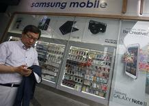 A man uses his mobile phone in front of a Samsung mobile shop in Seoul July 4, 2013. Samsung Electronics Co Ltd estimated its April-June operating profit rose 47 percent to a record 9.5 trillion won ($8.3 billion), lifted by the late April launch of its flagship Galaxy S4 smartphones. Picture taken on July 4, 2013. REUTERS/Kim Hong-Ji