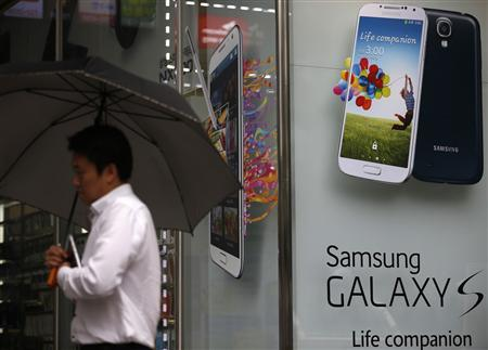 A man holding an umbrella walks past an advertisment promoting Samsung Electronics' Galaxy S4 in Seoul July 4, 2013. REUTERS/Kim Hong-Ji