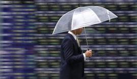 Мужчина с зонтом проходит мимо экранов брокерской конторы в Токио 12 июня 2013 года. Фонды региона EMEA (Европа, Ближний Восток, Африка) зафиксировали приток средств после пяти недель отрицательной динамики, и российские акции на этом фоне получили максимальную выгоду от улучшения настроений инвесторов. REUTERS/Toru Hanai