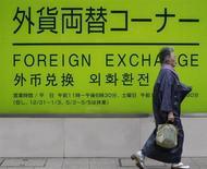 Женщина проходит мимо рекламы обменного пункта банка в Токио 30 ноября 2009 года. Доллар повсеместно растет в пятницу после того, как два крупнейших центробанка Европы удивили рынки мягкими прогнозами. REUTERS/Kim Kyung-Hoon