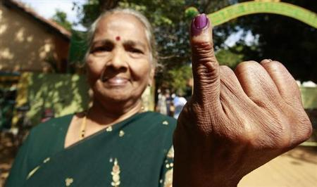 A Tamil woman shows her ink-marked finger after she cast her vote during a local government election in Jaffna about 304 km (184 miles) north of Colombo, July 23, 2011. REUTERS/Dinuka Liyanawatte/Files