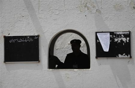 Policemen are seen silhouetted at the entrance of the Sargodha jail in Punjab province on June 24, 2010. REUTERS/Faisal Mahmood
