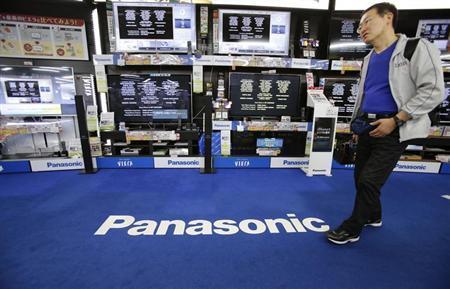 A man walks past Panasonic Corp's Viera televisions displayed at an electronics store in Tokyo May 9, 2013. REUTERS/Toru Hanai