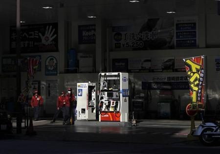 Workers stand to wait for customers at a gas station in Tokyo March 15, 2012. REUTERS/Toru Hanai