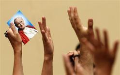 Человек держит фотографию папы Иоанна Павла II во время чтения молитвы Ангел Господень папой Бенедиктом XVI в летней резиденции в Кастель Гандольфо 29 июля 2012 года. Скончавшийся в 2005 году папа римский Иоанн Павел II будет причислен к лику святых, сообщил в пятницу Ватикан. REUTERS/Alessandro Bianchi