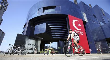 A biker pedals past the Guthrie Theater in the heart of the old milling district in Minneapolis, Minnesota July 2, 2013. REUTERS/Eric Miller