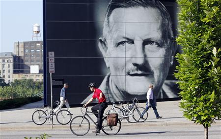 A cyclist rides past a giant portrait of Sir Tyrone Guthrie, creator of the Guthrie Theater in the heart of the old milling district in Minneapolis, Minnesota July 2, 2013. REUTERS/Eric Miller
